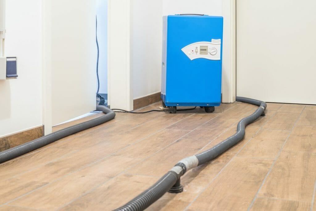 Blauer Bautrockner zur Estrichtrocknung nach Wasserschaden