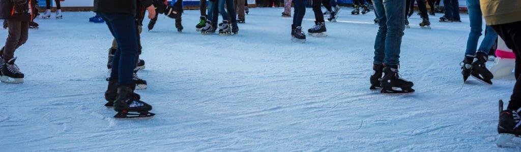 Menschen mit Schlittschuhen auf mobiler Eisbahn