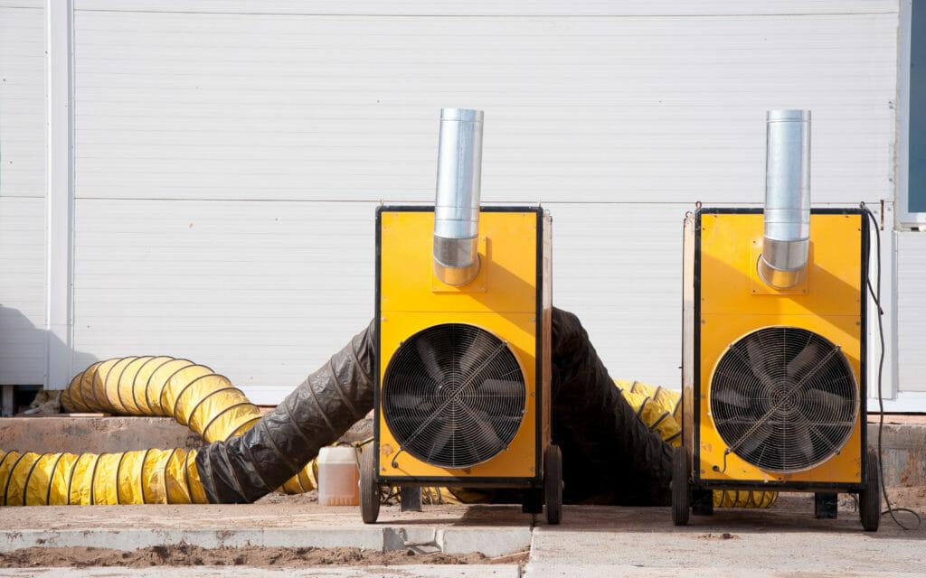 Warmlufterzeuger führen warme Luft über Warmluftschläuche in das Gebäude