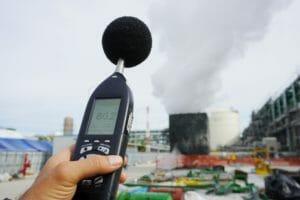 Schallpegelmessgerät in Hand vor Industrieanlage
