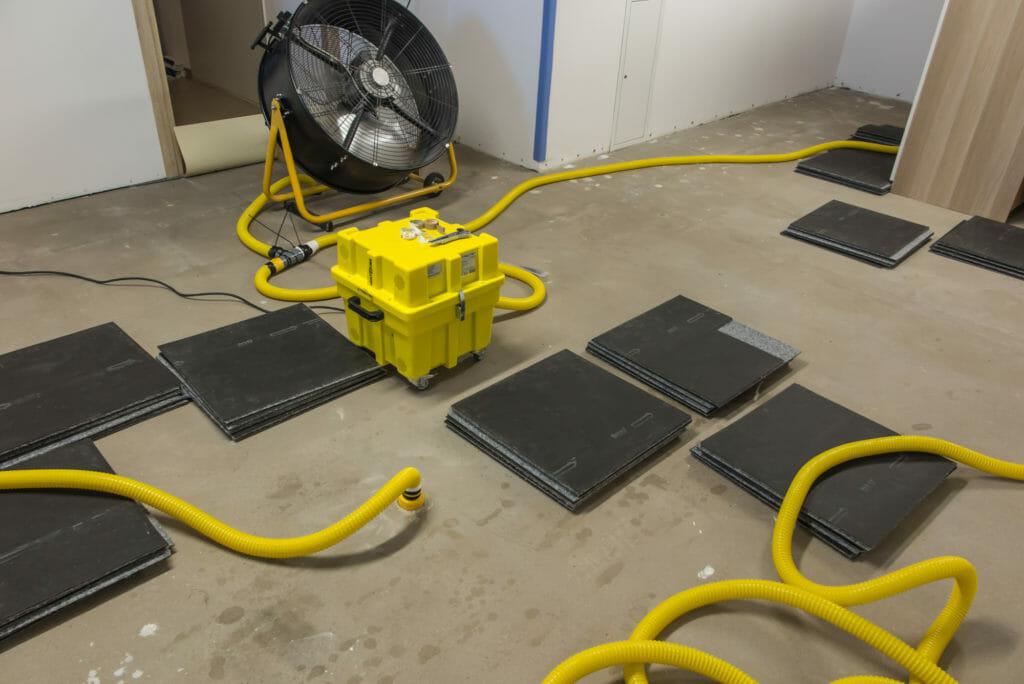 Gelber Estrichtrockner neben Ventilator und Schläuchen bei der Estrichtrocknung