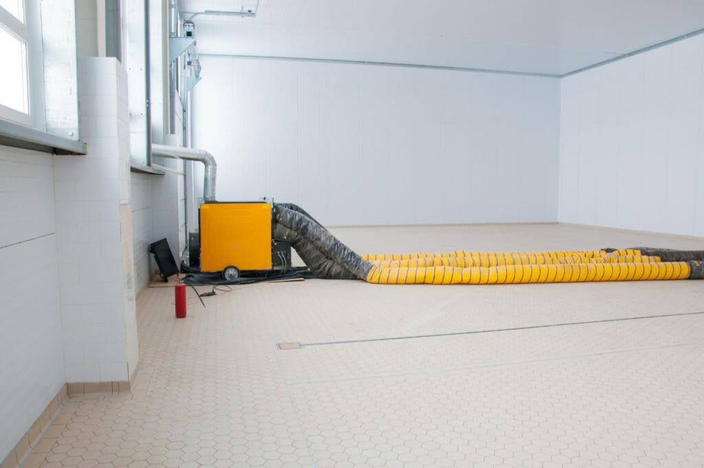 Gelbe mobile Dieselheizung mit Schläuchen auf Baustelle